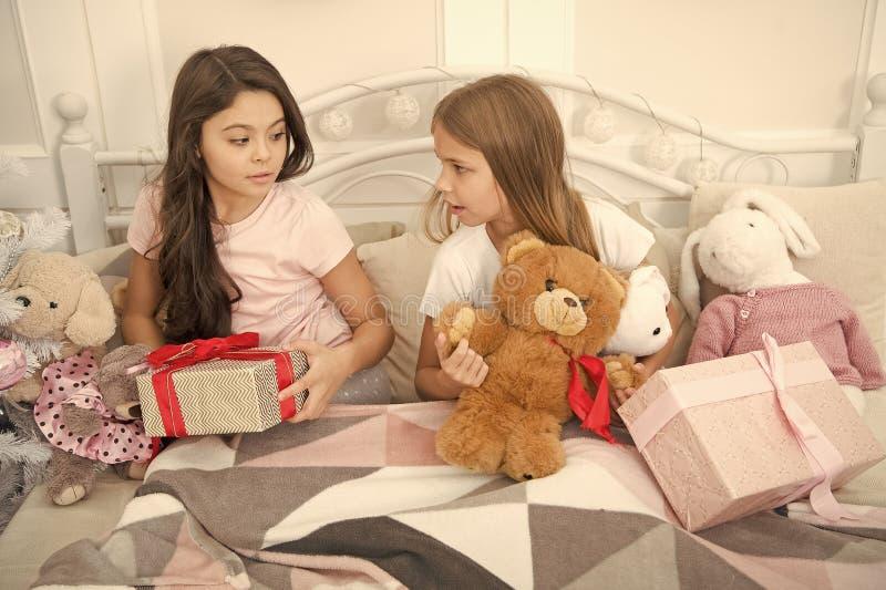 Feliz Natal e ano novo feliz As crian?as pequenas felizes guardam caixas de presente Meninas com presentes na cama abertura imagens de stock royalty free