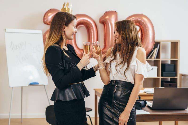 Feliz Natal e ano novo feliz As jovens mulheres estão comemorando o feriado no escritório fotografia de stock royalty free