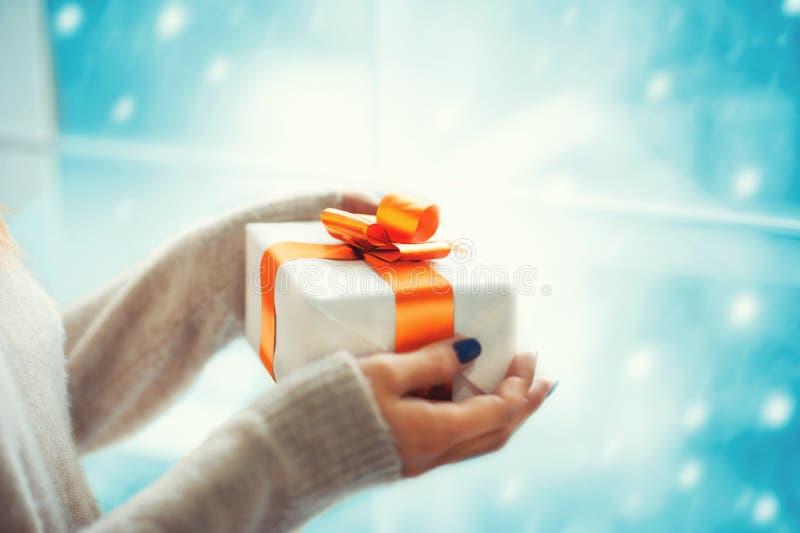 Feliz Natal e ano novo feliz! Feche acima das mãos fêmeas que mantêm a caixa atual interna ao ficar na frente da janela em flocos imagem de stock royalty free