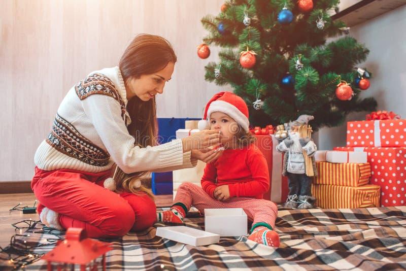 Feliz Natal e ano novo feliz Imagem bonita da mãe e da criança que sentam-se junto A mulher alimenta a menina pequena miúdo imagem de stock