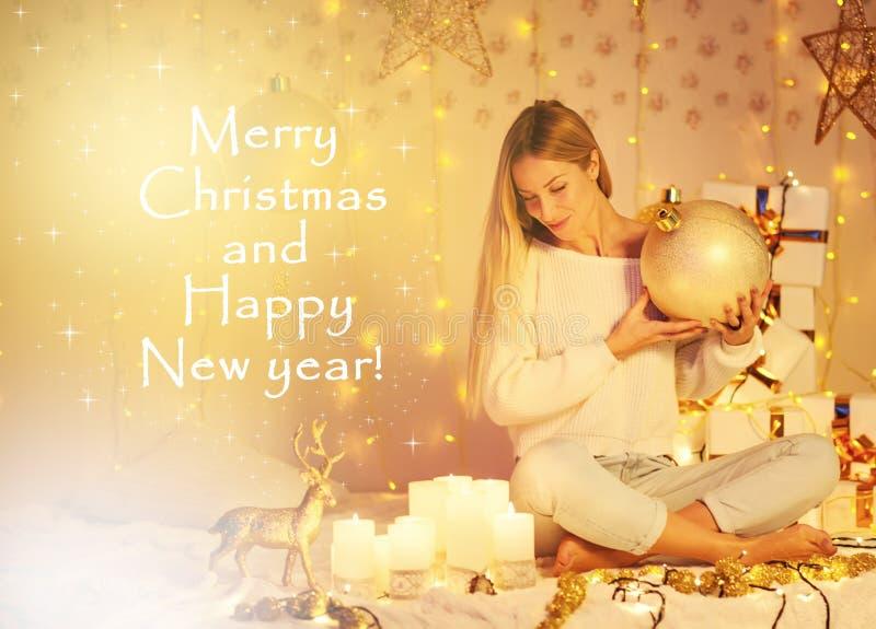 Feliz Natal e ano novo feliz! jovem mulher bonita com cabelo longo na camiseta feita malha que senta luzes decoradas internas imagem de stock