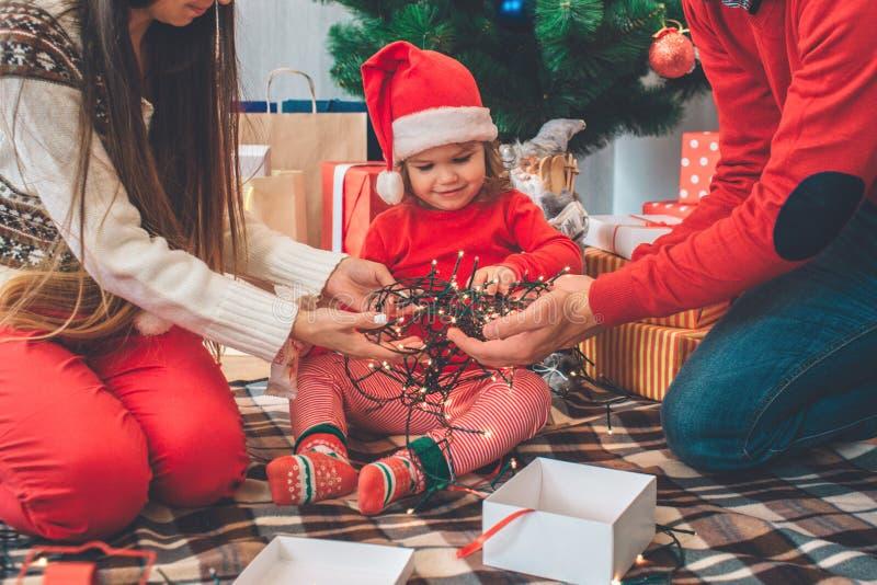 Feliz Natal e ano novo feliz A menina satisfeita e pequena senta-se entre pais e olhar em luzes de Natal isso fotos de stock