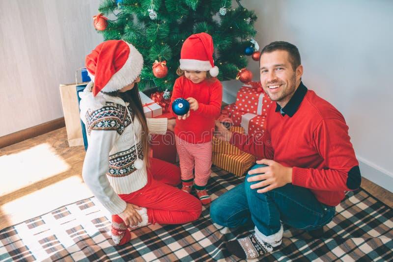 Feliz Natal e ano novo feliz O homem positivo olha na câmera e sorri Senta-se além da menina e da jovem mulher eles imagem de stock