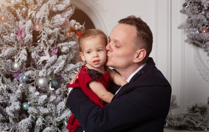 Feliz Natal e ano novo feliz O paizinho em um terno de negócio mantém sua filha vestida em um vestido vermelho elegante foto de stock