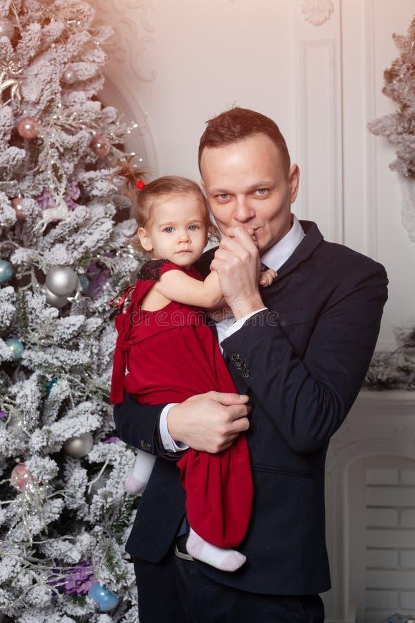 Feliz Natal e ano novo feliz O paizinho em um terno de negócio mantém sua filha vestida em um vestido vermelho elegante fotografia de stock royalty free