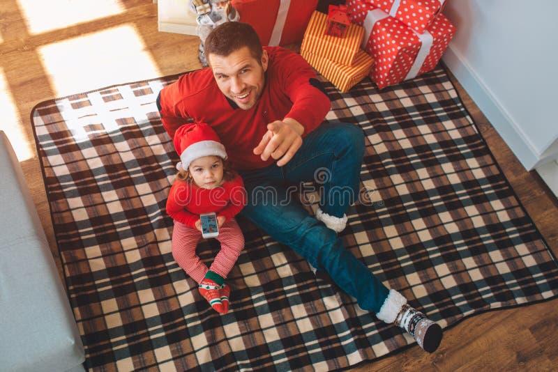 Feliz Natal e ano novo feliz O paizinho novo senta-se na cobertura com criança e no olhar na câmera Sorri e aponta sobre foto de stock