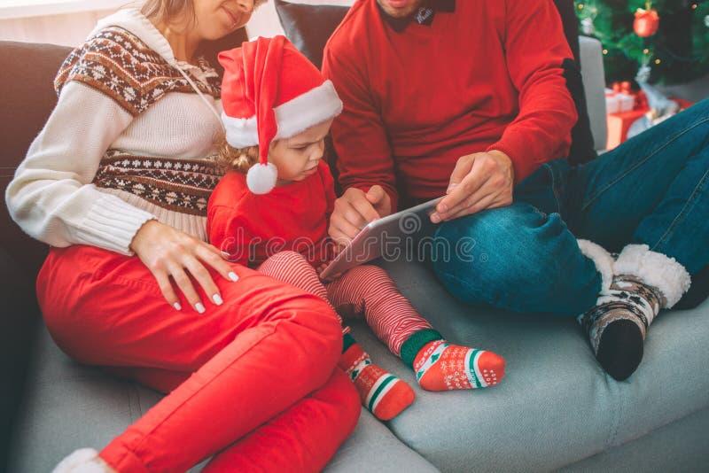 Feliz Natal e ano novo feliz A opinião do corte da família a menina pequena senta-se entre seus pais Guarda a tabuleta e os ponto fotografia de stock royalty free