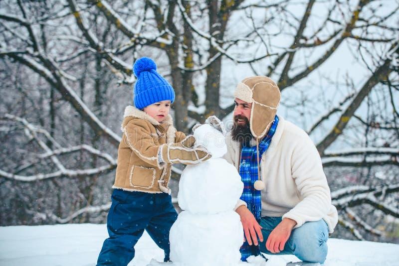 Feliz Natal e ano novo feliz Pai feliz e filho que fazem o boneco de neve na neve Homem engraçado feito a mão da neve Fam?lia imagem de stock
