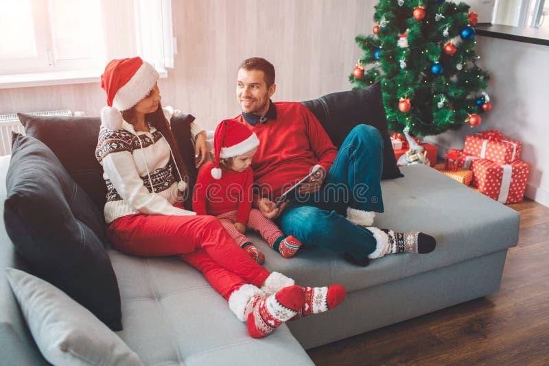 Feliz Natal e ano novo feliz Parenst calmo e calmo que encontra-se no sofá com criança Olham se Homem imagens de stock royalty free