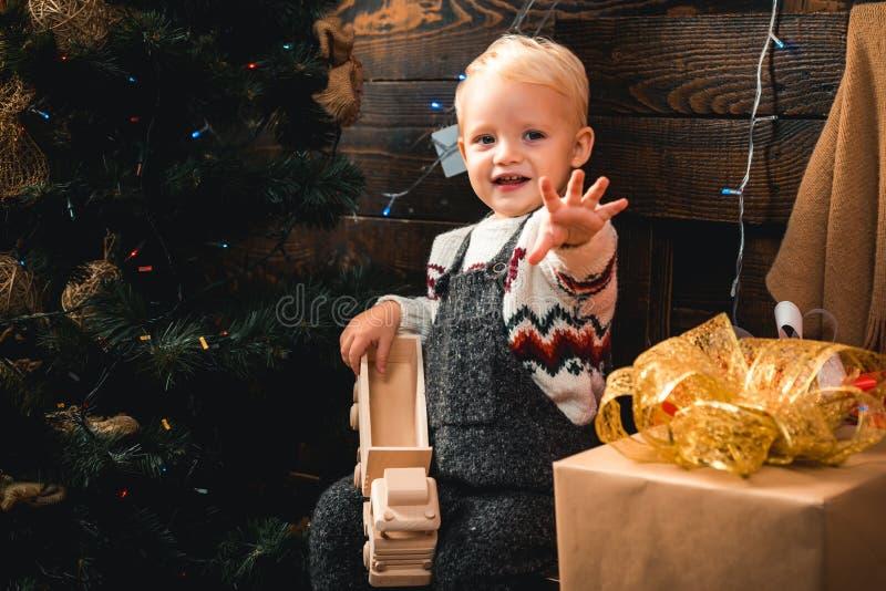 Feliz Natal e ano novo feliz Presente bonito da abertura da criança pequena perto da árvore de Natal O menino da criança que ri e foto de stock