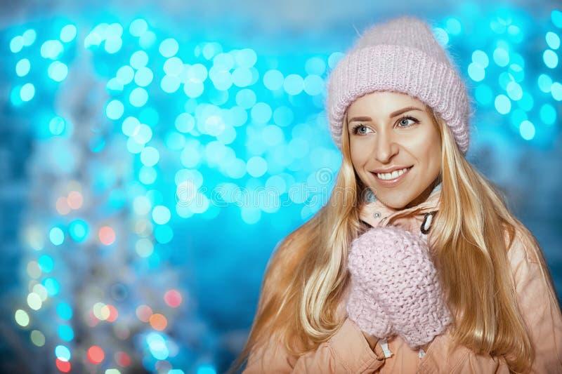 Feliz Natal e ano novo feliz! Retrato da mulher bonita alegre feliz no chapéu e em mitenes feitos malha que fica exterior imagens de stock royalty free