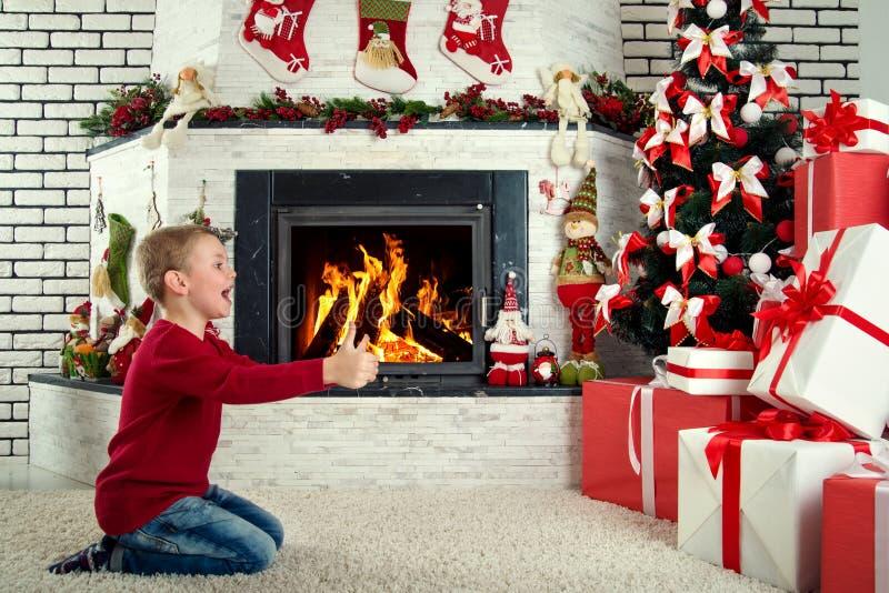 Feliz Natal e boas festas! A criança bonito encontrou muitos presentes sob a árvore de Natal fotos de stock
