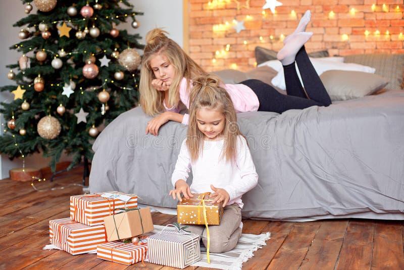 Feliz Natal e boas festas Crianças bonitos alegres que abrem presentes Crianças que têm o divertimento perto da árvore na manhã foto de stock