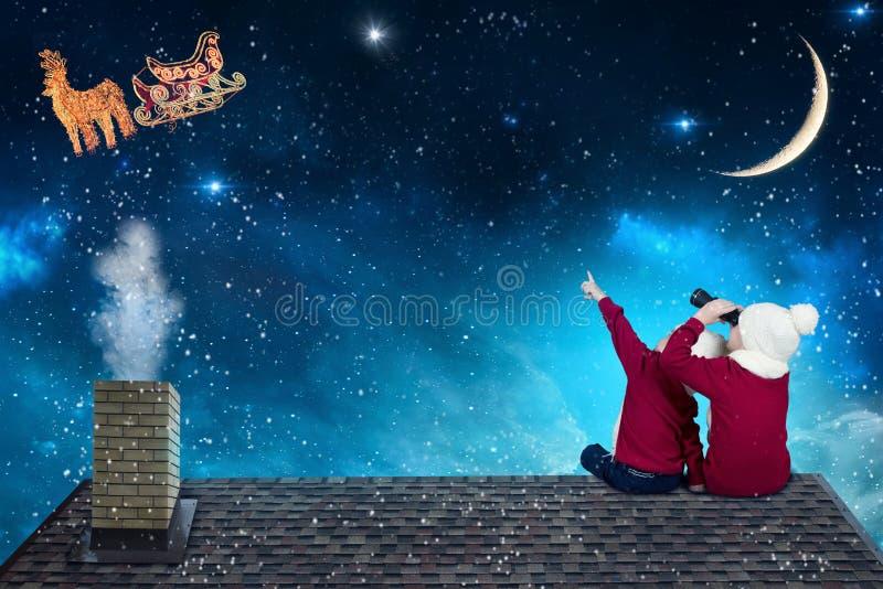 Feliz Natal e boas festas! Dois irmãos mais novo que sentam-se no telhado e que olham o voo de Santa Claus em seu trenó contra imagem de stock