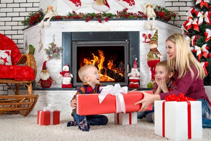 Feliz Natal e boas festas! Mãe e filhos que sentam-se pela chaminé e pelos presentes abertos do Natal de Santa fotografia de stock royalty free