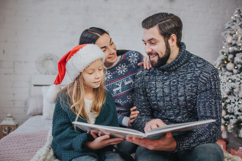 Feliz Natal e boas festas mamã alegre, paizinho e sua menina bonito da filha lendo um livro Pai e criança pequena fotografia de stock royalty free