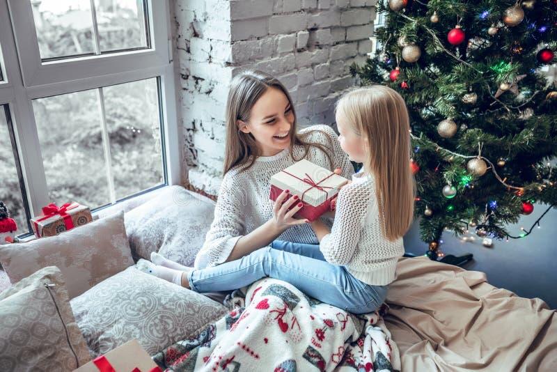 Feliz Natal e boas festas! Mamã alegre e sua menina bonito da filha que trocam presentes imagens de stock