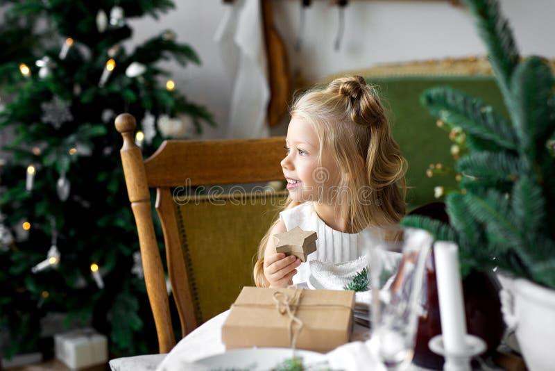 Feliz Natal e boas festas Menina bonito alegre da criança que abre um presente de Natal imagens de stock