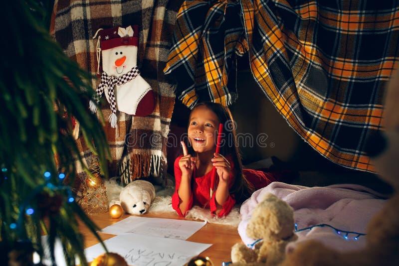 Feliz Natal e boas festas A menina bonito da criança pequena escreve a letra a Santa Claus perto da árvore de Natal imagens de stock royalty free