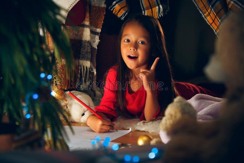 Feliz Natal e boas festas A menina bonito da criança pequena escreve a letra a Santa Claus perto da árvore de Natal foto de stock royalty free