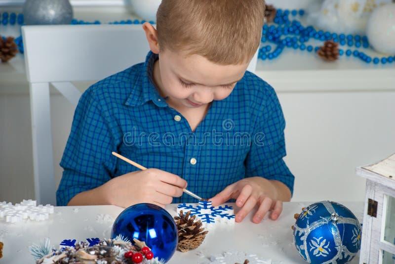 Feliz Natal e boas festas! Um menino que pinta um floco de neve A criança cria decorações para o interior do Natal fotos de stock royalty free