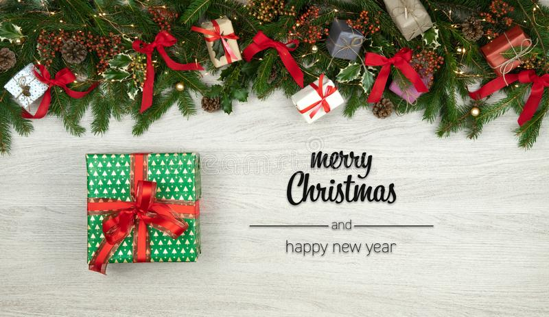 Feliz Natal e cumprimentos do ano novo feliz na madeira branca vertical da vista superior com ramos, fitas, luzes e presente do p foto de stock