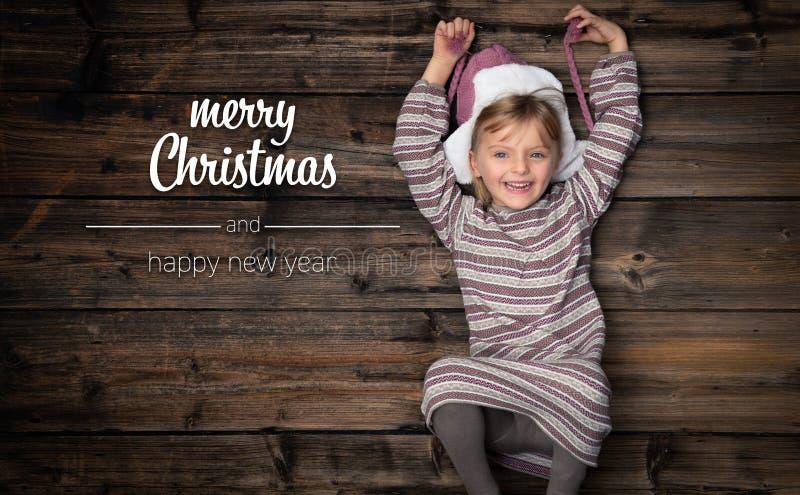Feliz Natal e cumprimentos do ano novo feliz na madeira escura vertical do vintage da vista superior Menina feliz bonita da crian fotos de stock royalty free