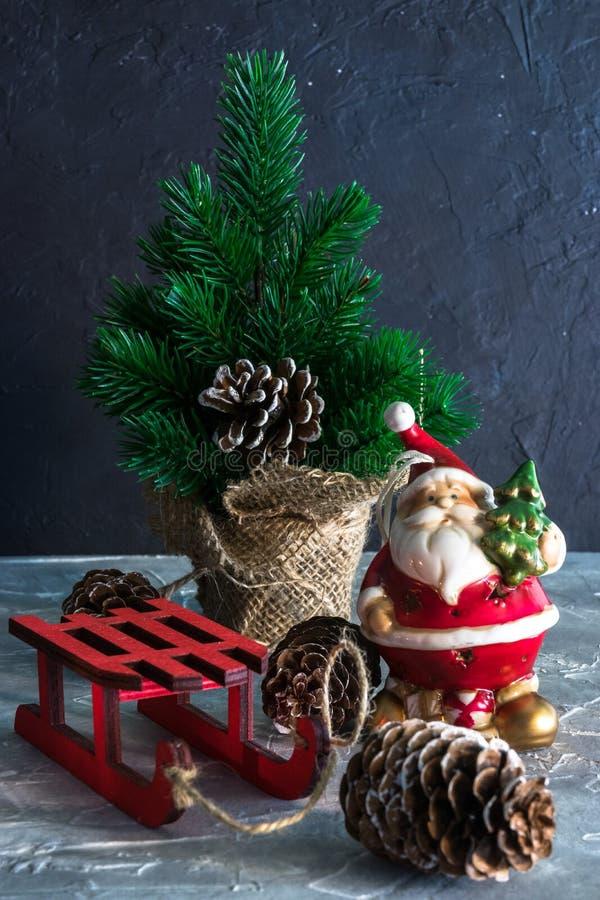 Feliz Natal e um ano novo feliz Um brinquedo de Santa Claus, uma vela ardente e um trenó Feriados do Natal grupo de ornam do Nata fotografia de stock