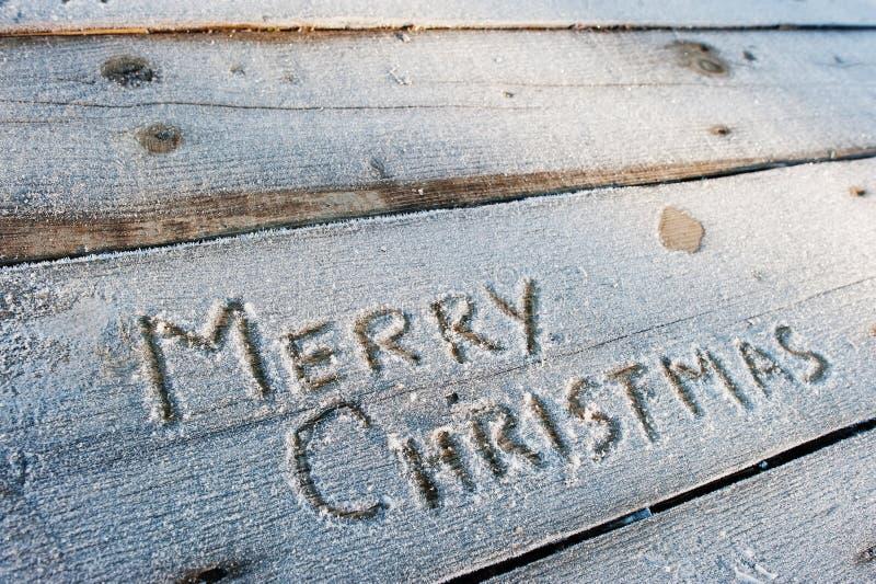 Feliz Natal escrito em um fundo de madeira com geadas fotografia de stock royalty free