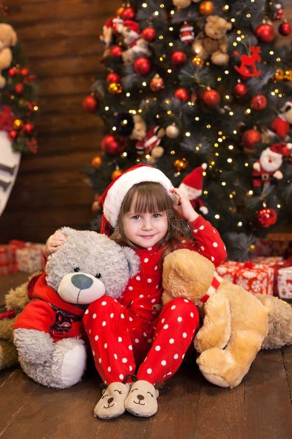 Feliz Natal, feriados felizes Ano Novo 2020 Menina de pijama vermelha sentada com presentes na árvore de Natal nos vivos imagem de stock royalty free