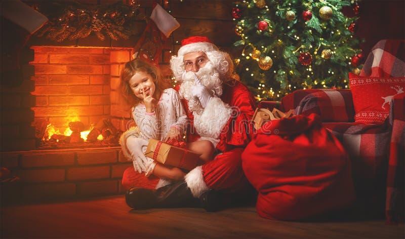 Feliz Natal! menina de Papai Noel e de criança na noite no Chr fotos de stock