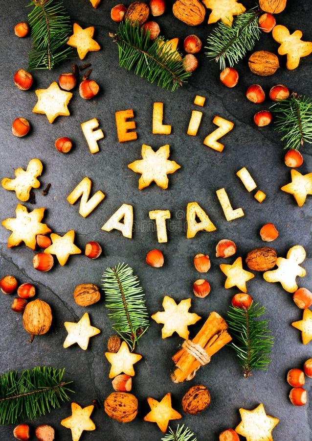 FELIZ NATAL-PLÄTZCHEN En-Portugiese der Wort-frohen Weihnachten mit gebackenen Plätzchen, Weihnachtsdekoration und Nüssen auf Sch stockfotografie