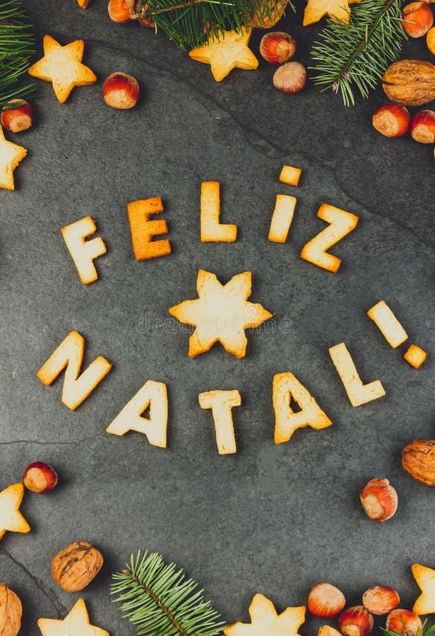 FELIZ NATAL-PLÄTZCHEN En-Portugiese der Wort-frohen Weihnachten mit gebackenen Plätzchen, Weihnachtsdekoration und Nüssen auf Sch stockbilder