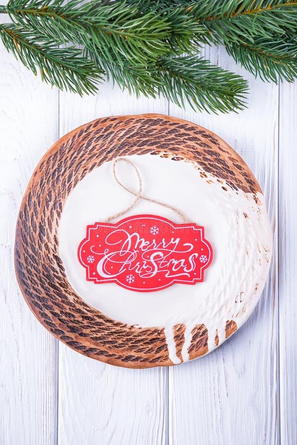 Feliz Natal Ramo de árvore cerâmico feito à mão da placa e do Natal em um fundo branco imagens de stock