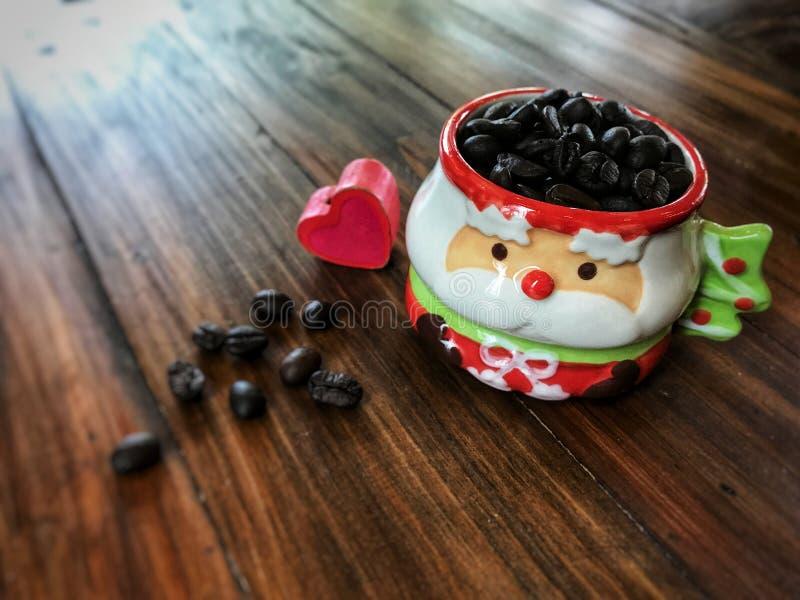 Feliz Navidad, corazón rojo y granos de café en Santa Claus Cup linda imagenes de archivo