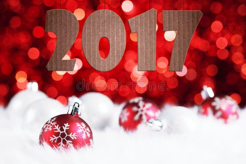 Feliz Navidad 2017 en la textura de madera en sitio de la perspectiva con la pared roja chispeante del bokeh y el piso de madera  fotos de archivo libres de regalías
