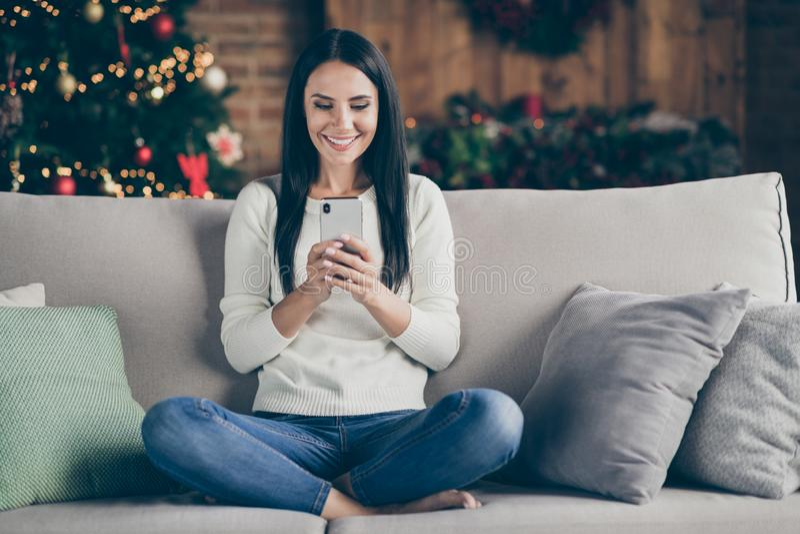 Feliz Navidad. Fotografía completa de la sentada festiva positiva divan usar el tipo de smartphone felicitaciones de nuevo año d fotos de archivo