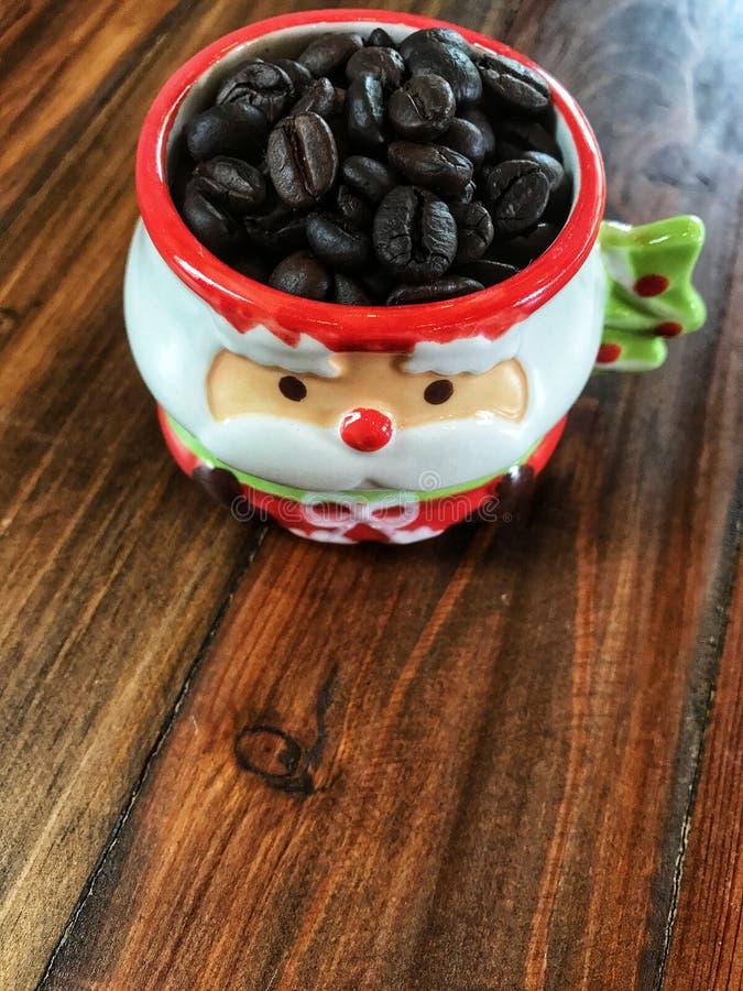 Feliz Navidad, granos de café en Santa Claus Cup linda foto de archivo