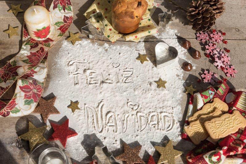 Feliz Navidad, texto espanhol feito com a farinha, cercada por Chris foto de stock