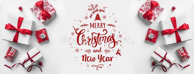 Feliz Navidad tipográfica en el fondo blanco con las cajas de regalo y la decoración roja imagen de archivo libre de regalías
