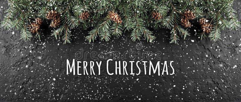 Feliz Navidad tipográfica en fondo oscuro del día de fiesta con el marco de las ramas del abeto, conos del pino fotos de archivo libres de regalías