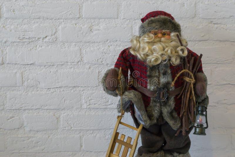 Feliz Navidad, una muñeca de Papá Noel en el primer que sostiene un trineo y una linterna aislados en un fondo blanco de la pared imagen de archivo
