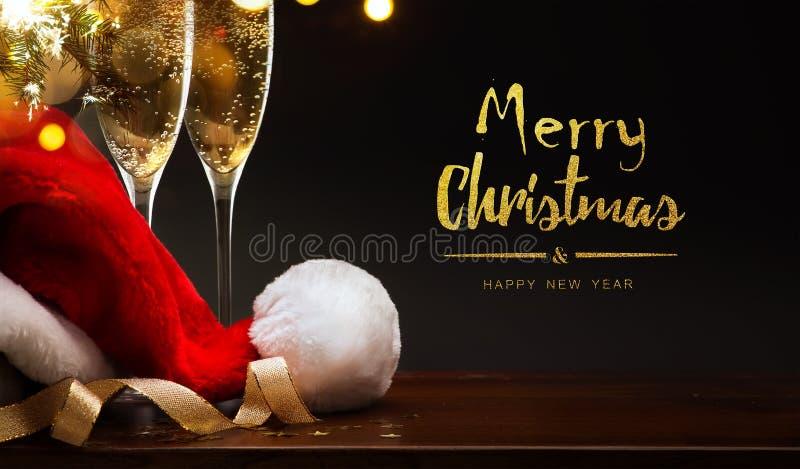 Feliz Navidad y Feliz Año Nuevo; champán y sombrero de Papá Noel imagen de archivo