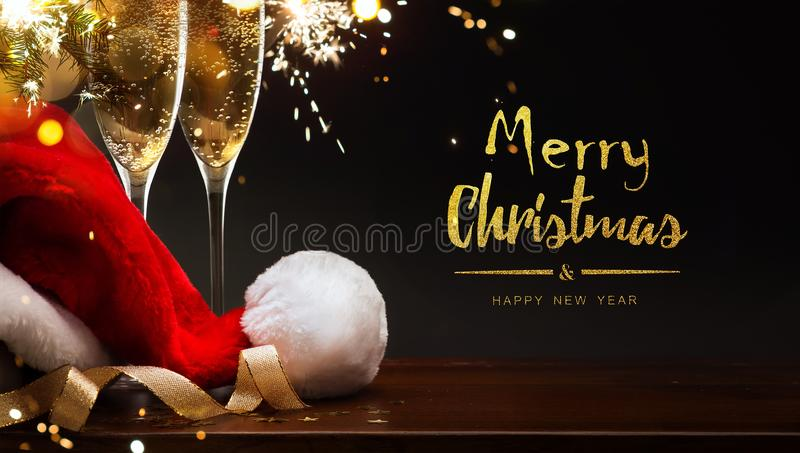 Feliz Navidad y Feliz Año Nuevo; champán y sombrero de Papá Noel imágenes de archivo libres de regalías
