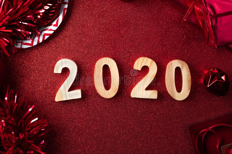 Feliz Navidad y Feliz Año Nuevo 2020 en fondo rojo la vista superior de la malla, caja de regalo, bola, cinta adorna en la tabla  foto de archivo