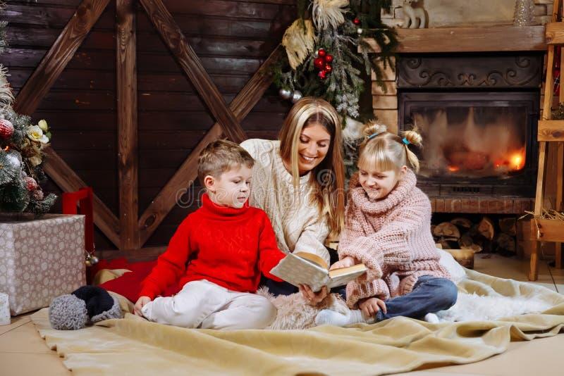 Feliz Navidad y Feliz Año Nuevo Familia hermosa en interior de Navidad Madre joven bonita que lee un libro a ella fotos de archivo