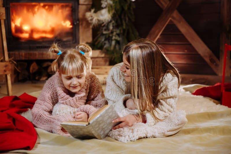 Feliz Navidad y Feliz Año Nuevo Familia hermosa en interior de Navidad Madre joven bonita que lee un libro a ella imagenes de archivo
