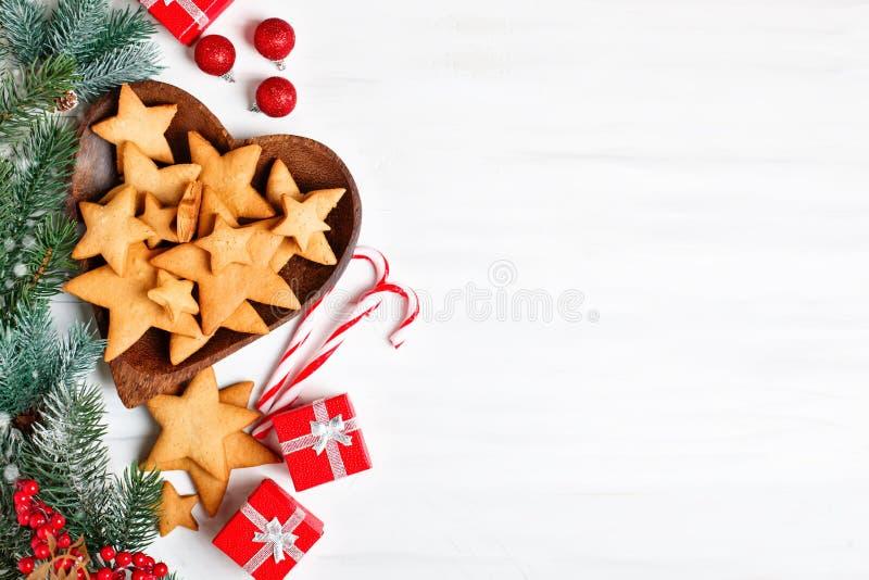 Feliz Navidad y Feliz Año Nuevo Galletas, regalos y ramas del abeto en una tabla de madera blanca Foco selectivo fotos de archivo