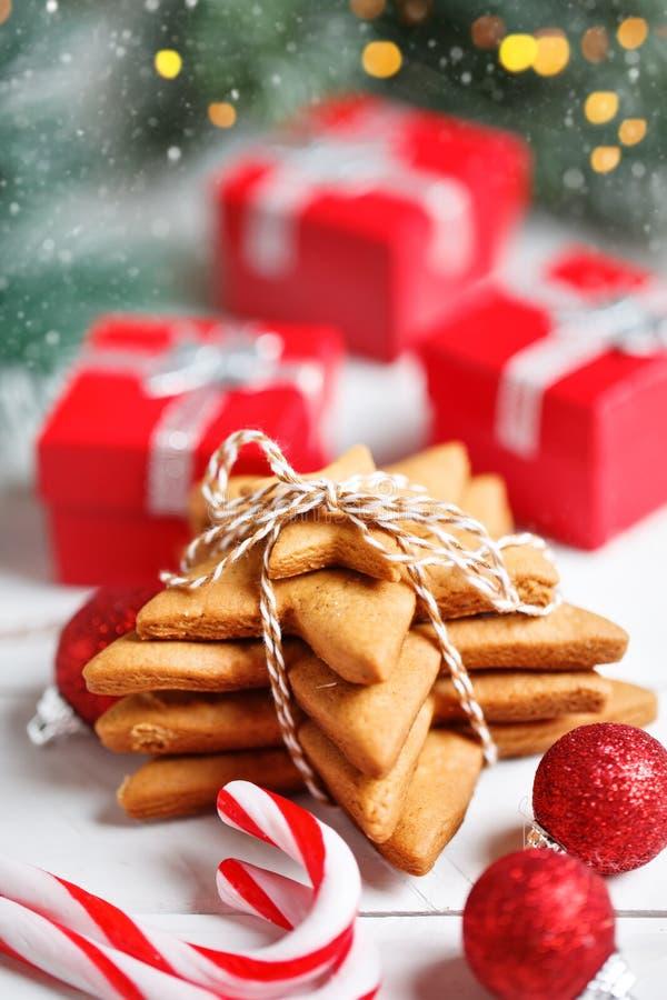 Feliz Navidad y Feliz Año Nuevo Galletas, regalos y ramas del abeto en una tabla de madera blanca Foco selectivo imagenes de archivo