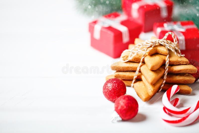 Feliz Navidad y Feliz Año Nuevo Galletas, regalos y ramas del abeto en una tabla de madera blanca La Navidad imagen de archivo libre de regalías